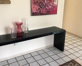 long black lacquer table, framed acrylic and crystal vases