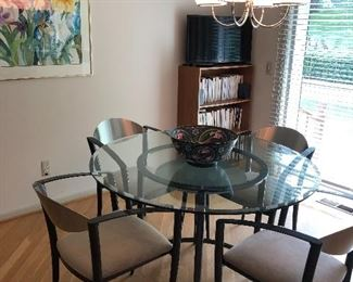 round glass kitchen table with 4 chairs, bookcase and framed watercolor