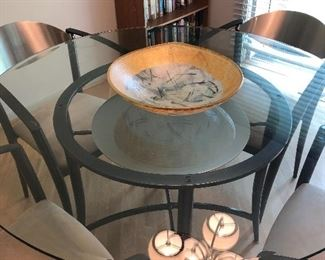 round dining table with glass top and 4 chairs and gold-leaf bowl