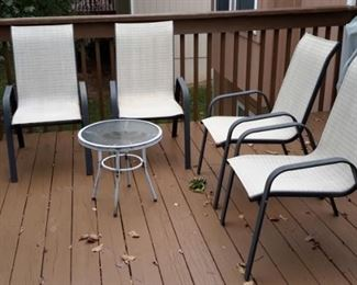 Four patio chairs and one glass top side table.