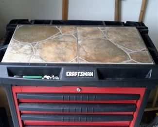 Craftsman tool chest with casters, peg boards on the side and added ceramic tile on top.