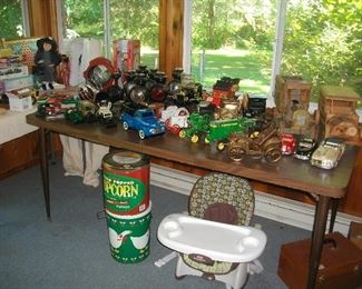 "Misc trucks, tractors, gas head lamps, tins, etc.  The seat under the table is a ""high chair"" that's low."