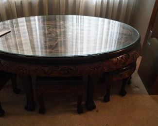 glass top, wood carved coffee table with 6 foot stools