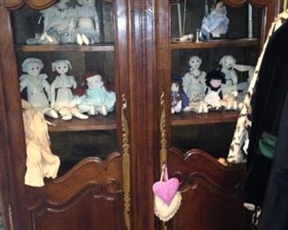 Display armoire filled with rag dolls
