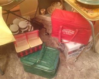 Metal picnic basket, Coca Cola soft carrier and vintage plaid sandwich carrier.  Behind it is a luncheon set.