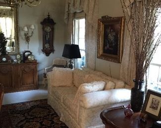 Very comfortable loves eat, oriental rug, painting with gold gilded frame and picture light.