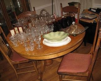 oak pedestal table with one leaf in and 4 pressed back chairs
