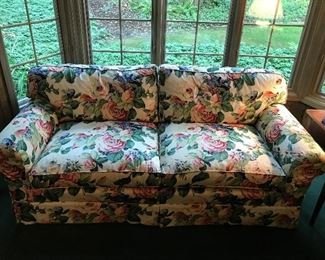 Upholstered couch with floral design.