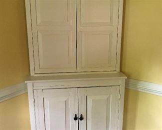 Large, older corner cabinet painted white.