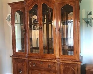 2 piece china hutch with glass shelves and lighting.