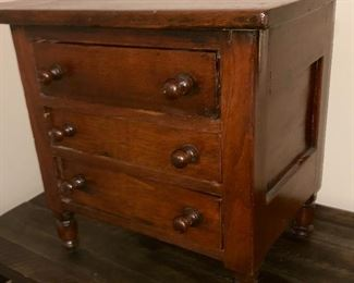 Tennessee made chest with three drawers for doll clothes, treasures or jewelry;  hand cut dovetail drawers, beveled panel back resting on turned legs. This piece may have been refinished, if so the newer finish is old now.