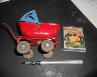 Small metal baby carriage and book