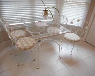 """Smaller size  wrought iron table with 4 chairs.   66"""" x 32"""" approximately"""