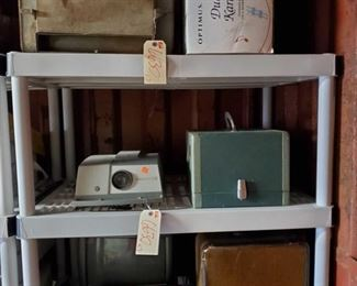 """6630: Vintage TV, Radio, Typewriter, Projectors and Cases, Car Cooler and Karaoke System LOTS of vintage things to see in this lot! *a Samsung portable TV AM/FM radio model BT-123AJ (1984), AC 120 volts, 60Hz, 11 watts-DC12 volts 6 watts. Includes manual and cords. *a medium sized (appx 20"""") television *a vintage brown leatherette typewriter case *a vintage Sears Citation 1960's portable typewriter with original case. This is a cream-colored model with gray interior, black case. Made in the 1960's still in good condition. *a vintage AirEquipt 135 35mm 2x2 slide projector with remote changer *a vintage Argus 300 automatic slide projector with slide changer in box – great condition *a Polar Breeze automatic car cooler (circa 1940's) *an Optimus dual-cassette karaoke system, all in one portable entertainment center in box"""