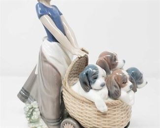 """8504:  Lladro """"Litter of Fun"""" Girl Pushing Puppies Figurine Here is Lladro's retired """"Litter of Fun"""" figurine #5364 (1986-2000) is an adorable fine porcelain figurine of a little girl pushing a stroller basket of puppies. Measures approx 8.5"""" Low Estimate: 180 High Estimate: 250"""