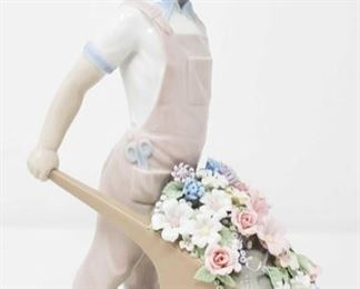 """8505:  Boy Pushing Wheelbarrow with Flowers Lladro SUCH a cute little figurine! Laldro's """"Boy Pushing Wheelbarrow"""" #1283 features a young boy in overalls and straw hat pushing a wheelbarrow full of beautiful flowers. Handmade and hand painted in Valencia, Spain.  Measures approx 9.5"""" tall Low Estimate: 350 High Estimate: 895"""