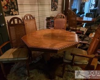 """8600: Octagon Shaped Dining Room Table with 4 Chairs EXCEPTIONALLY GORGEOUS!! This Octagon shaped table with carved heart shaped lattice edges sits on a sturdy pedestal with four-point base anchored in decorative bended belts of wrought iron. Accompanied by four tall-back caned chairs, exquisitely detailed with cathedral window style splay upper back and rounded spindles on each end. Seats are wide, covered in beige fabric with gold and gray accents, green piping. Pretty unique and special! Table measures approx 44"""" x 30"""""""