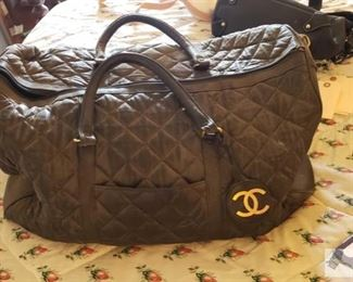 8704: Not Authenticated Chanel bag The duffel bag shown here is an apparent Chanel designer model (circa 2000's) though not authenticated but bears a makers label. Crafted from black nylon this bag features dual flat leather handles and a black-tone hardware, zip closure, side zip pocket.