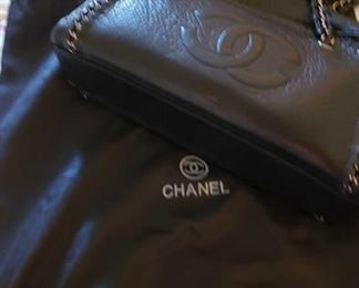 8707:  Not Authenticated Chanel handbag This small Chanel handbag has not been authenticated but closely resembles the black aged calfskin leather braided handle bag with ruthenium hardware, interior zippered compartment and full upper zip closure. Braided them follows around the front and back of the purse giving it attractive characteristics.
