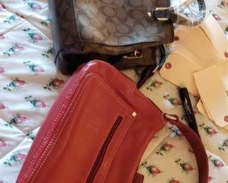8709:  2 Coach Handbags Shown here are two Coach purses, one is new with plastic and tags! A black purse with black handles model #6825 and the other is a red leather handbag with front zippered compartment and top zippered closure.