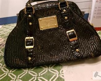 8712:  Louis Vuitton Handbag This shiny black leather handbag bears the official Louis Vuitton Inventeur seal. This gorgeous textured handbag with gold hardware will be a beautiful accessory to your evening wear.