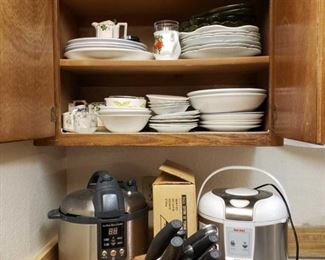 """8800: Aroma Rice Cooker, Breville Pressure Cooker, Pots, Pans and other Assorted Kitchen Supplies GREAT kitchen lot here!!! Lots of dishware, cups, glasses, cream and sugar bowls, dessert plates, decorator service plates, some china pieces. Also in this lot: two rice cookers, a butcher knife block with knives, a Gordon handheld knife sharpener, a Saladmaster vegetable processer with unused parts and instruction manual, an 8"""" Windsor candle lead crystal table lamp, posts and pans, electric fryer, several food containers and plastic ware, a tea bell, a Sunbeam Oskar Jr. chopper, strainers, misc flatware, bowls, a bamboo and teakwood rice bowl with serving spoon, several various utensils, serving trays, mugs and mug sets, highball glasses new in box, mini crock pot, Saladmaster Estate Porzellan heirloom collectible cups from Germany, tea cups from JOHANN HAVILAND GERMANY… there are many hidden treasures in this lot!! Look through carefully!!"""