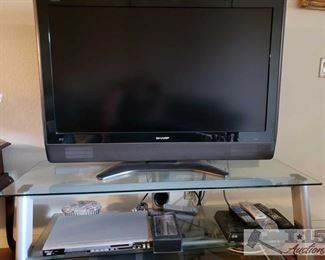 """8853:  45"""" Sharp TV, DVD Player, Dish Reciever, TV Stand and More Three electronic items you need for your entertainment room: * a Sharp 45"""" television model number LC-45D40U 52"""" x 22"""" x 21"""" * an AStar 6800 DVD player features full compatibility with DVD, CD, Kodak Picture CD, CD-R, and CD-RW. Has multiple playback modes, dynamic spectrum display, and digital audio output. * a Mitsubishi Hi Fi U52 4-head video cassette recorder with intelligent picture, twin digital tracking, and 200 index time search function This lot includes a metal and glass stand for all three!"""