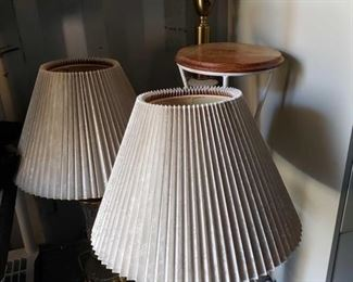 8912: 3 Lamps and Pot Stand This lot features two crystal and brass lamps with pleated beige shades, a brass, ceramic, and white glass floor lamp, and a white metal plant stand with round wooden top.Tallest lamp measures approximately 4' tall