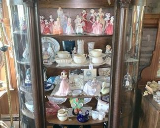 Curved glass showcase (We have 2), filled with figurines and porcelain.)