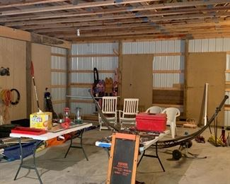 Pole barn is filled with various items including lanterns, out door chairs, ladders, creeper, skis, lawn tools etc..