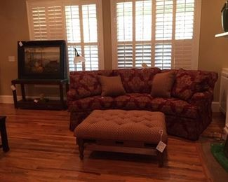 beautiful sofa and ottoman with pull out tray, floor lamp, lots of books