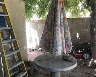 CONCRETE TABLE WITH UMBRELLA.  ALSO, LADDERS AND TWO LAWN MOWERS.