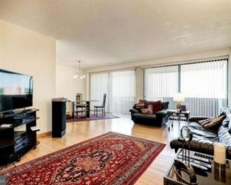 living room: leather couch, leather love seat, two glass end tables, lamp, speakers, and stereo (TV and TV stand not for sale),  candle holders, Persian wool rug