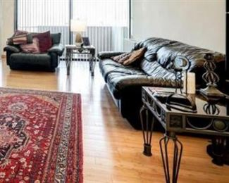 living room: leather couch, leather love seat, two glass end tables, lamp, Persian wool rug, candle holders