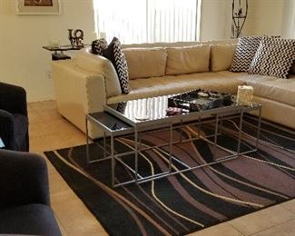 Beautiful neutral like new sectional sofa with modern black and brown rug along with a glass coffee table that has 2 side tables that fit under the table or just pull them out a bit for a bigger coffee table.