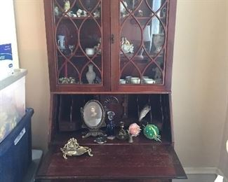 Vintage secretary with various collectibles.