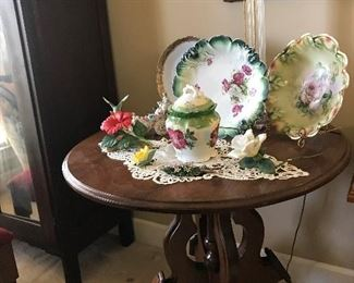 Round table with display plates and floral and bird figurines, tall lamp