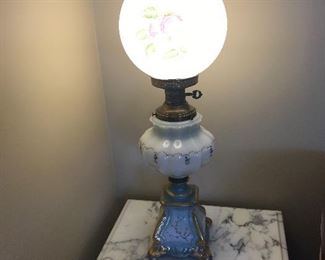 Antique GWTW lamp on one of a pair of marble top end tables