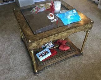 End table matches one of the coffee tables with brass legs and caned shelf
