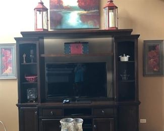 The media unit is actually in four parts - each side of the unit come off (and would look good flanking a fireplace) and the top, or bridge, removes - so you could put quite a large TV on the remaining credenza.  The sides and below are great for storage, video game consoles, audio equipment, etc.