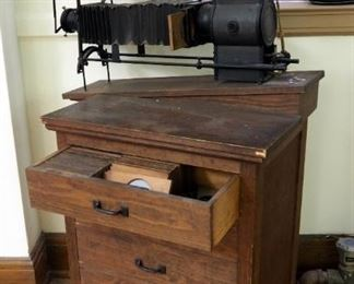 "The M.C. Lilley And Co. Antique Electric Slide Projectors With Rolling Wood Projector Table Includes Antique Wood Slides In Top Drawer 40"" X 34""X 21"