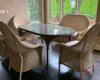 Lloyd Flanders wicker set. Glass top with 4 chairs and bench seat. Table is 40 X 71. The seat cushions were reupholstered last year in a very neutral cream fabric. Synthetic wicker can be used in or outdoors.