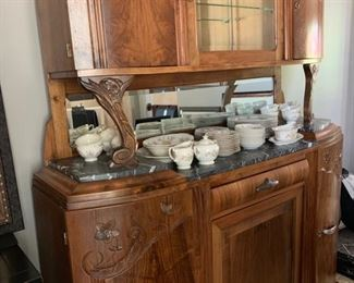 Antique sideboard with marble top and hutch in medium wood tones with wood carvings.