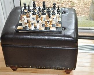 """Dark brown leather tufted storage ottoman with nail heads. 23""""w x 18""""h x 18""""d. Shown with vintage marble chess set."""