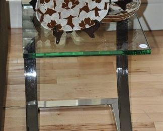 """Contemporary glass side table with chrome base, 16""""w x 20""""h x 16""""d shown with pretty brown and white floral ceramic serving pieces."""