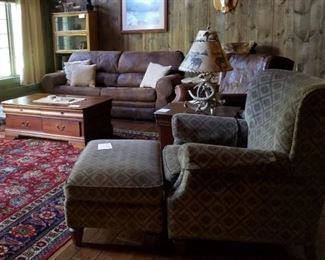 Leather sleeper sofa,  barrister bookcase, chair and ottoman,  large coffee table with storage drawers, end tables,  antler lamps