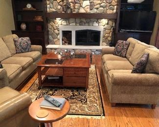 Matched set of Ethan Allen couches, area rug, large coffee table with drawer and shelf storage, large TV and more artwork and collectibles on shelves