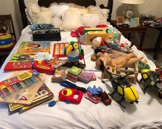 Bed full of vintage toys and lace pillows