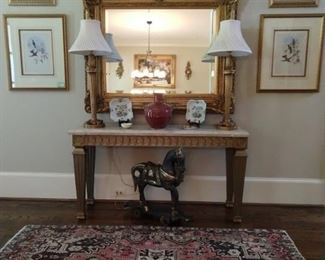 Huge gold wall mirror, with beveled glass, travertine topped gold wood console table, pair of gold candlestick table lamps, beautiful vintage Persian Heriz, wooden Trojan horse on wheels, pair of hummingbird lithographs and pair of botanicals, all well framed/matted.