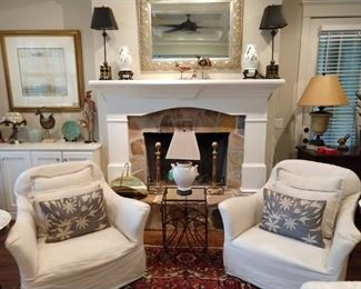 One of two PAIR of Verellen linen armchairs, antique English brass andirons, brass kindling holder, pair of harlequin candlestick lamps, wrought iron/glass side table, pottery jug table lamp.